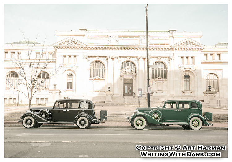 """""""Welcoming the new car models"""" by Art Harman. The introduction of the latest models is always a time of excitement, and these new beauties gleamed in the sunshine. A shot of serendipity to capture these cars in a perdiod setting, and I processed the photo to emulate the look of 1930s photography."""
