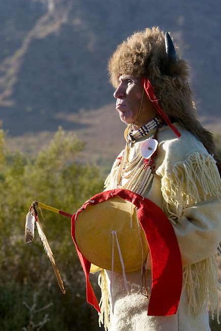 Native American man of the Sioux Nation dressed in traditional regalia and bison headdress holds a medicine stick and shield.