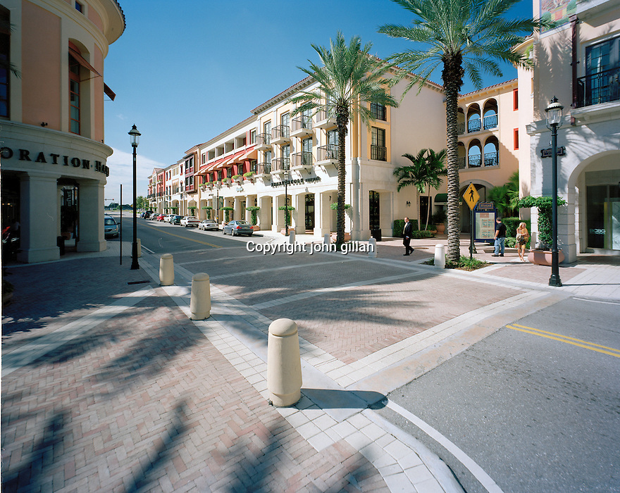Street scene view of City Place in Palm Beach showing storefronts and Date palms.