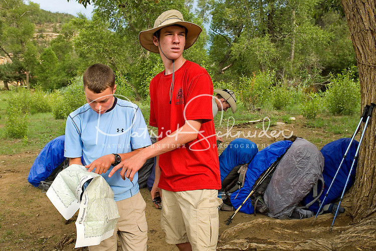 Photo story of Philmont Scout Ranch in Cimarron, New Mexico, taken during a Boy Scout Troop backpack trip in the summer of 2013. Photo is part of a comprehensive picture package which shows in-depth photography of a BSA Ventures crew on a trek. In this photo, a Boy Scout/Venture Crew Leader reviews his map with a fellow crew member during a break from hiking in the backcountry of the Philmont Scout Ranch.<br /> Photo by travel photograph: PatrickschneiderPhoto.com
