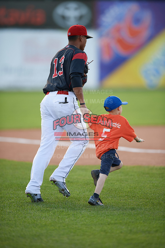 """Batavia Muckdogs left fielder Jhonny Santos (13) runs out to the field with a young """"Star of the Game"""" before a game against the West Virginia Black Bears on June 24, 2017 at Dwyer Stadium in Batavia, New York.  The game was suspended in the bottom of the third inning and completed on June 25th with West Virginia defeating Batavia 6-4.  (Mike Janes/Four Seam Images)"""