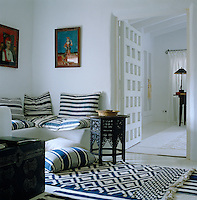 A built-in corner bench is covered in blue and white striped cushions in this impromptu sitting room at the door to the master bedroom
