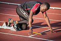 Tuesday 15th July 2014<br /> Pictured: Christian Malcolm <br /> RE: Welsh Sprinter Christian Malcolm positioned in the starting blocks holding a relay baton about to compete in the Welsh Athletics International 4x100m relay at the Cardiff International Sports Stadium, Wales, UK. His last race on home soil.