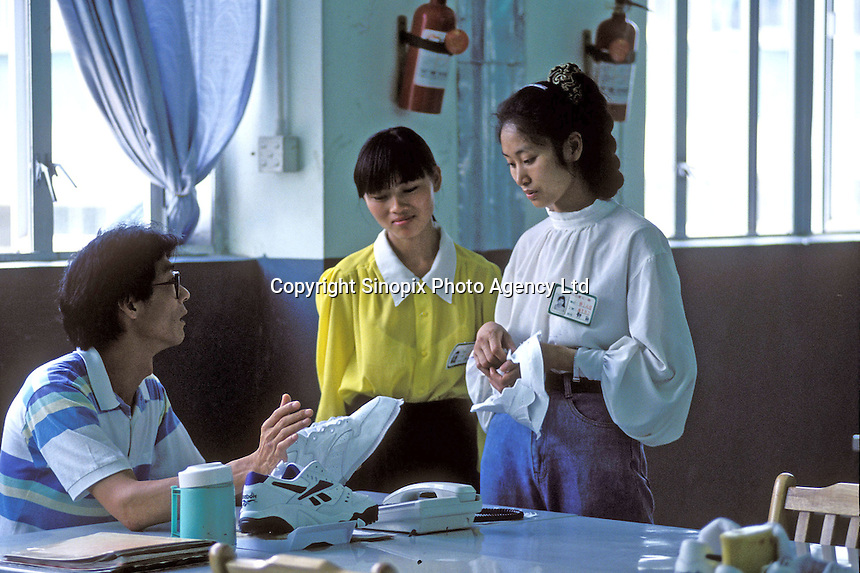 A manager instructs two supervisors at the Yuen Yue Reebok factory in Zhuhai, China...