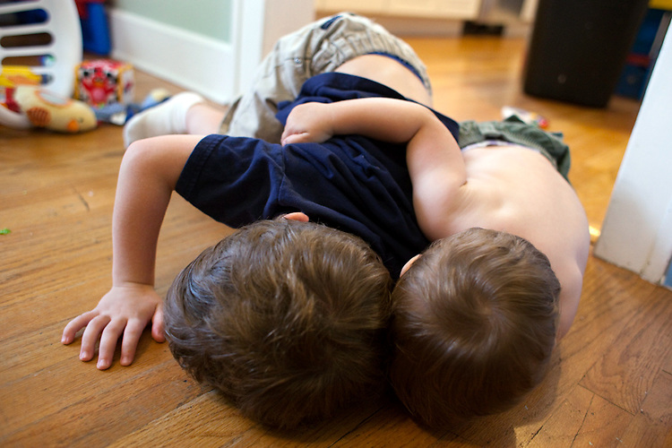 My younger son, age one and not yet a walker, right, grabs his brother, four, from behind and pulls him to the floor.