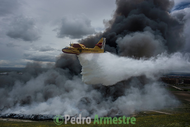 A seaplane discharges water over the tyres burning in an uncontrolled dump near the town of Sesena, after a fire broke out early on May 13, 2016. A huge waste ground near Madrid where millions of tyres have been dumped was on fire today, releasing a thick black cloud of toxic fumes that officials worry could harm residents nearby. © Pedro ARMESTRE