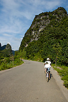 Young Chinese man riding in tandem with a European boy along foliage covered cliffs, Yangshuo, Guangxi, China.