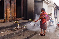 south America, Guatemala, Chichicastenango, woman shaking smoking incense  in front of church of Saint Thomas