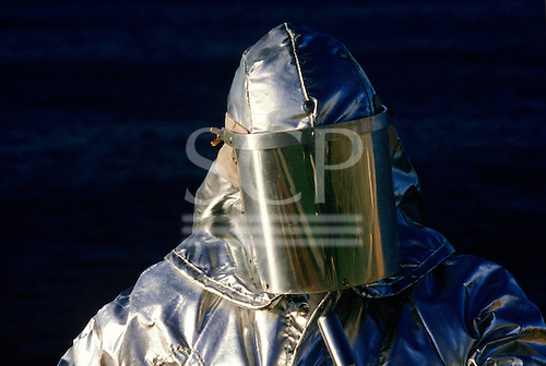 Rio de Janeiro, Brazil. Oil rig worker in silver fireproof suit and helmet with visor.