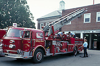 Firemen maintaining a hook and ladder fire engine.  May not be used in an elementary school dictionary. University Heights Ohio USA.