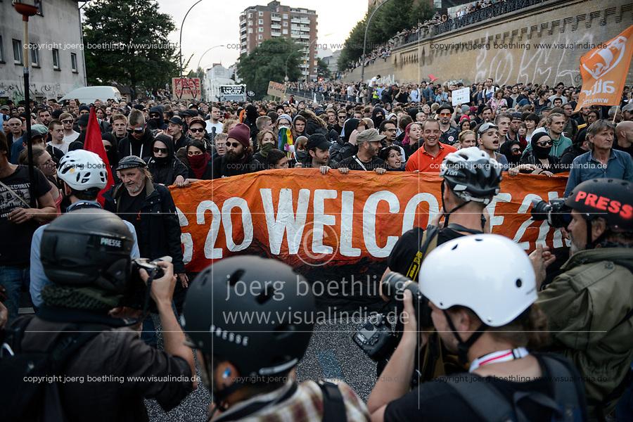 """GERMANY, Hamburg, protest rally """"G-20 WELCOME TO HELL"""" against G-20 summit in july 2017, black block with mummed people /DEUTSCHLAND, Hamburg, Landungsbruecken, Protest Demo WELCOME TO HELL gegen G20 Gipfel , vermummte Demonstranten des schwarzen Block,  links mit Ledermuetze Andreas Beuth, Anwalt des linksalternativen Zentrums """"Rote Flora"""""""