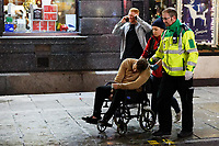 A man is taken away by wheelchair in Wind Street, Swansea, Wales  on Mad Friday, Booze Black Friday or Black Eye Friday, the last Friday night before Christmas Day, when traditionally people in the UK go out to celebrate the start of their holidays. Friday 22 December 2017
