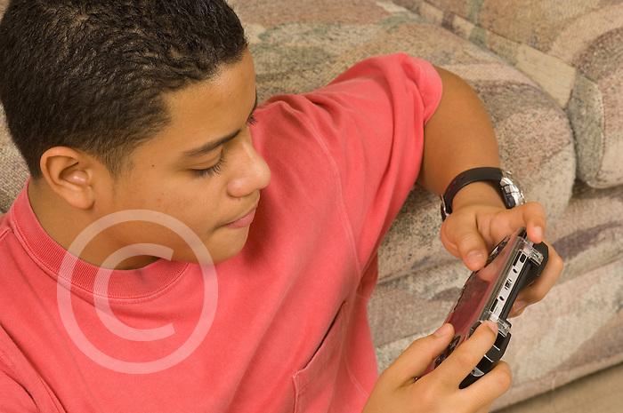 15 year old teenage boy at home playing handheld eletronic game horizontal Hispanic Puerto Rican