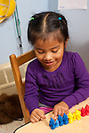 Education preschool 3-4 year olds girl counting colored plastic bears