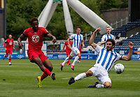 Wigan Athletic's Jamal Lowe shoots under pressure from Huddersfield Town's Christopher Schindler<br /> <br /> Photographer Alex Dodd/CameraSport<br /> <br /> The EFL Sky Bet Championship - Huddersfield Town v Wigan Athletic - Saturday 20th June 2020 - John Smith's Stadium - Huddersfield <br /> <br /> World Copyright © 2020 CameraSport. All rights reserved. 43 Linden Ave. Countesthorpe. Leicester. England. LE8 5PG - Tel: +44 (0) 116 277 4147 - admin@camerasport.com - www.camerasport.com
