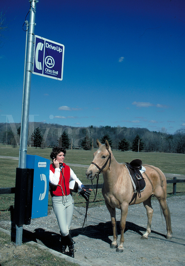 Woman riding a horse stops to use a public phone.