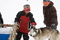 Kids in Shaktoolik pet a dropped dog before it goes on the airplane back to Unalakleet during Iditarod 2008