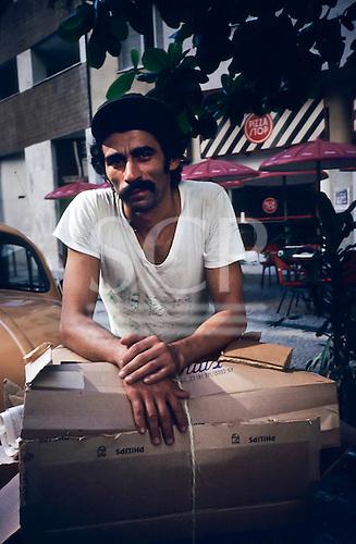 Rio de Janeiro, Brazil. Man collecting cardboard outside a Pizza Stop restaurant.