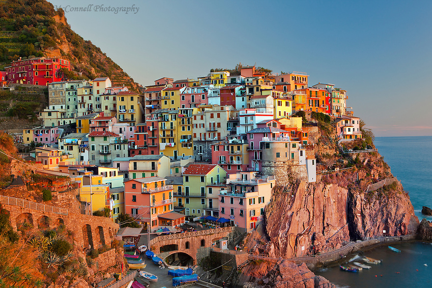 """""""Manarola Sunset""""<br /> Cinque Terre, Italy<br /> 2015<br /> <br /> The beautiful colors of Cinque Terre, Italy are at their best at sunset, as seen here in the town of Manarola.  From the north, the town is the fourth of five towns along the coast.  Access to Manarola is by train, boat, or hiking trail.  Without any automobiles, the small hamlet is an interesting place to explore."""
