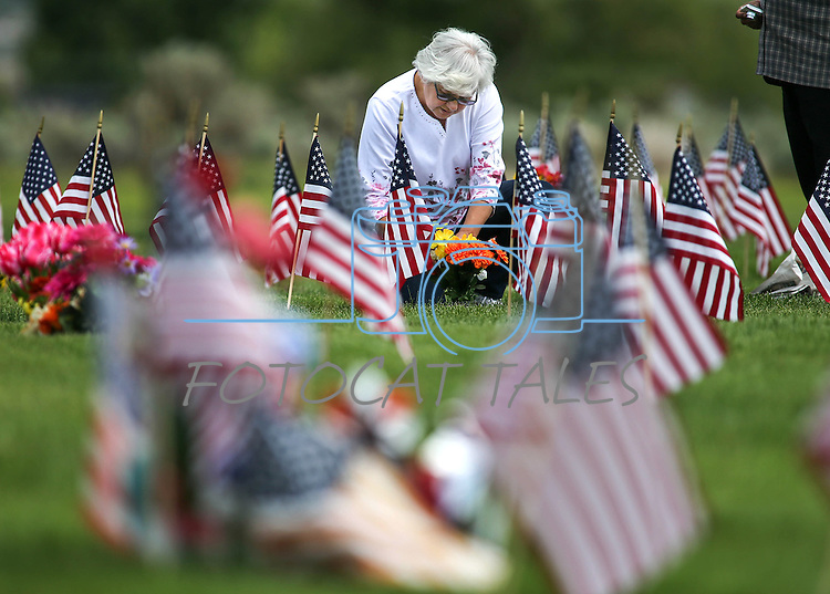 Renee Fredericks places flowers on her brother's grave in the veterans section of Lone Mountain Cemetery in Carson City, Nev., on Monday, May 25, 2015. <br /> Photo by Cathleen Allison