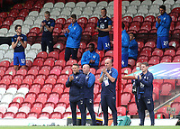 Wigan Manager, Paul Cook and his coaching staff and substitutes applaud the NHS and key workers ahead of kick-off as part of the 'Thank You Together' initiative during Brentford vs Wigan Athletic, Sky Bet EFL Championship Football at Griffin Park on 4th July 2020