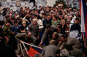 Moscow, Soviet Union<br /> August 24, 1991<br /> <br /> The body of a martyr is lowered into the ground following the Soviet coup d'état attempt (August 19-21, 1991), also known as the August Putsch or August Coup. A small group of the Soviet government officials briefly deposed president Mikhail Gorbachev in an attempted to take control of the country. The coup leaders were hard-line members of the Communist Party (CPSU) who felt that Gorbachev's reforms had gone too far in dispersing the central government's power to the republics - better known as perestroika. The coup collapsed in three days, and Gorbachev returned to power, crushing the Soviet leader's hopes that the union could be held together in a decentralized form.