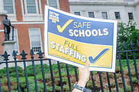 """A demonstrator holds a sign reading """"Safe Schools / Full Staffing"""" as people gathered outside the Massachusetts State House for a protest organized by the Massachusetts Teachers Association against current school reopening plans during the ongoing Coronavirus (COVID-19) global pandemic in Boston, Massachusetts, on Wed., Aug. 19, 2020. The teachers' union, alongside two other Massachusetts teachers' unions, organized the event as part of a mass day of action demanding that the school year starts with remote learning and switch to in-person learning only when health and safety standards can be guaranteed."""