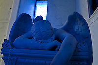 A statue of an angel bathed in blue light resides inside of a mausoleum in Metairie Cemetery, in New Orleans, Louisiana. In the New Orleans area the water table is too high to bury the dead in the ground. Mausoleums like these are very common.