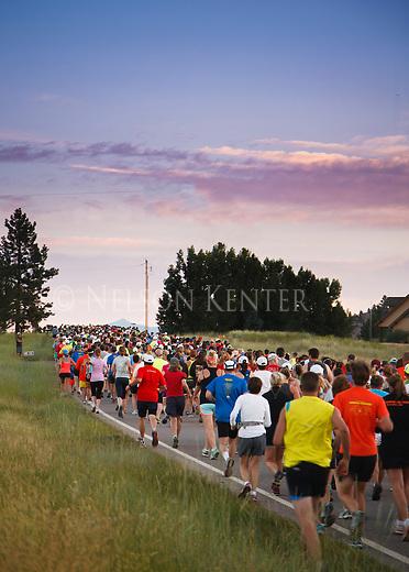 line of runners at the start of the missoula marathon before sunrise