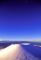 A volcanic cindercone covered with snow on top of Mauna Kea on the Big Island creates a stark image against a vivid blue sky.