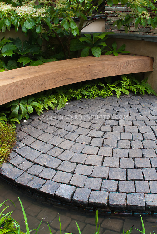 Garden bench and stone patio in circular curves, with moss, wall, hedges, ferns, Patio of bluestone pavers, with curving garden seat, stone pillar, wall, flowering viburnum shrub, shaded garden