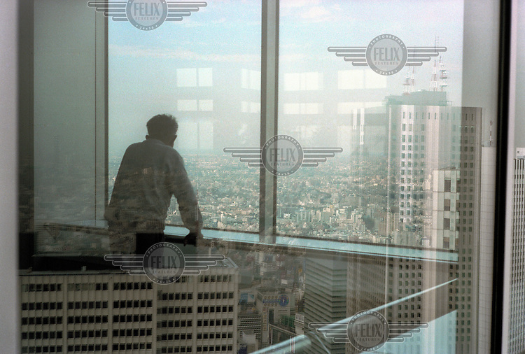 A man looks out across the city's skyline from the Tokyo Metropolitan Building.