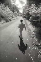 Man walking across country road<br />