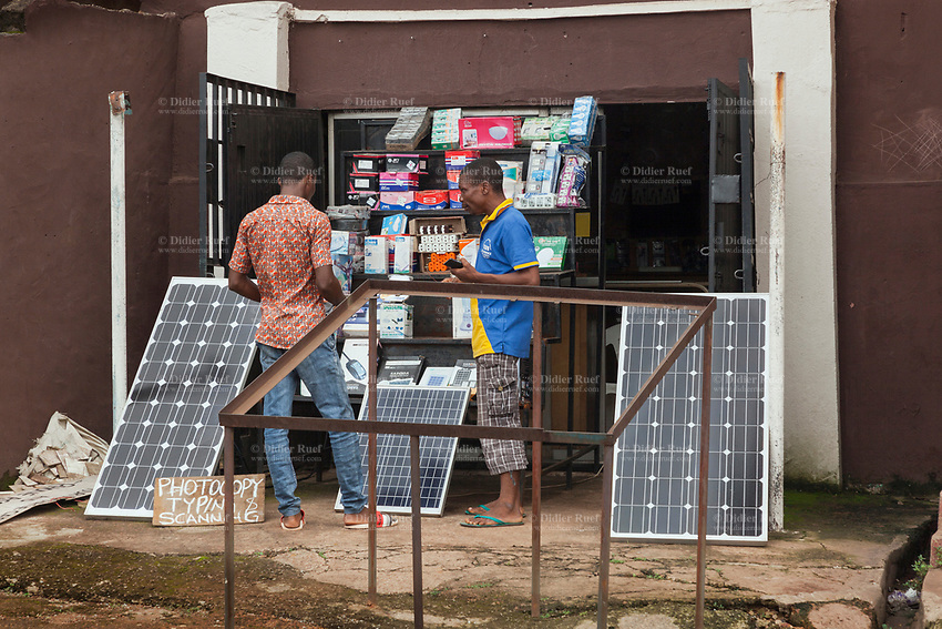 Nigeria. Enugu State. Enugu. Town center. Customers stand in front of a shop selling solar panels and various electronic items. Enugu is the capital of Enugu State, located in southeastern Nigeria. 15.07.19 © 2019 Didier Ruef