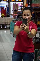 Yogyakarta, Java, Indonesia.  Batik Sales Room, Raradjonggrang Batik Factory.  Sales Clerk Photographing the Photographer.