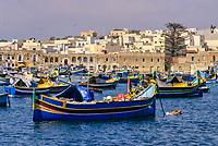 Marsaxlokk Harbor, Malta - Luzzu (traditional Maltese boat) in foreground.