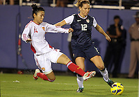 BOCA RATON, FL - DECEMBER 15, 2012: Lauren Cheney (12) of the USA WNT about to be tackled by Wang Dongni (14) of China WNT during an international friendly match at FAU Stadium, in Boca Raton, Florida, on Saturday, December 15, 2012. USA won 4-1.
