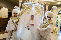 A bride at a traditional Kazakh wedding prepares to enter the wedding hall for her Betasher, a ceremony where the her face is revealed to the familes and guests.