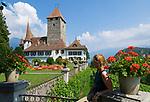 CHE, Schweiz, Kanton Bern, Berner Oberland, Spiez: Schloss Spiez am Thunersee - Frau sitzt auf Gelaender | CHE, Switzerland, Bern Canton, Bernese Oberland, Spiez: castle Spiez at Lake Thun - woman sitting on bench