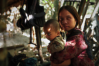 Relatives of veterans of the CIA Secret War, a Hmong mother and child, sit in the shade of their tatched hut in their hidden village in the Vientiane province of Laos on 27 November 2007. Thousands of Hmongs who fought or collaborated with the American CIA until communists took over the country in 1975 remain hidden in the jungles of Laos and remain regular targets of the Lao People's Army. The woman pictured had bullet wounds in her arm from a previous clash with the Lao People's Army