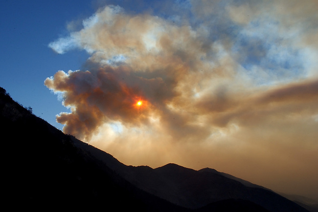 The sun peaks through heavy smoke in Lake Arrowhead, Calif., near the Rim of the World High School, Tuesday, Oct. 28, 2003. (AP Photo/Paul Sakuma)