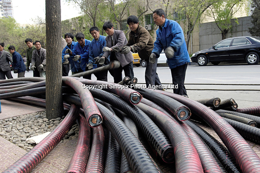 Chinese workers replace electric cables on a street in Beijing, China. .