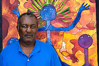 Leroy Exil, artist, at home with his paintings.