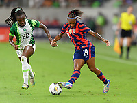 AUSTIN, TX - JUNE 16: Crystal Dunn #19 of the United States passes the ball in front of Michelle Alozie #22 of Nigeria during a game between Nigeria and USWNT at Q2 Stadium on June 16, 2021 in Austin, Texas.