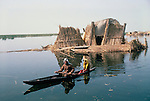 Marsh Arabs. Southern Iraq. Marsh Arab man with daughter in boats with traditional reed built island home called a kibasha. Haur al Mamar or Haur al-Hamar marsh collectively known now as Hammar marshes Iraq 1984