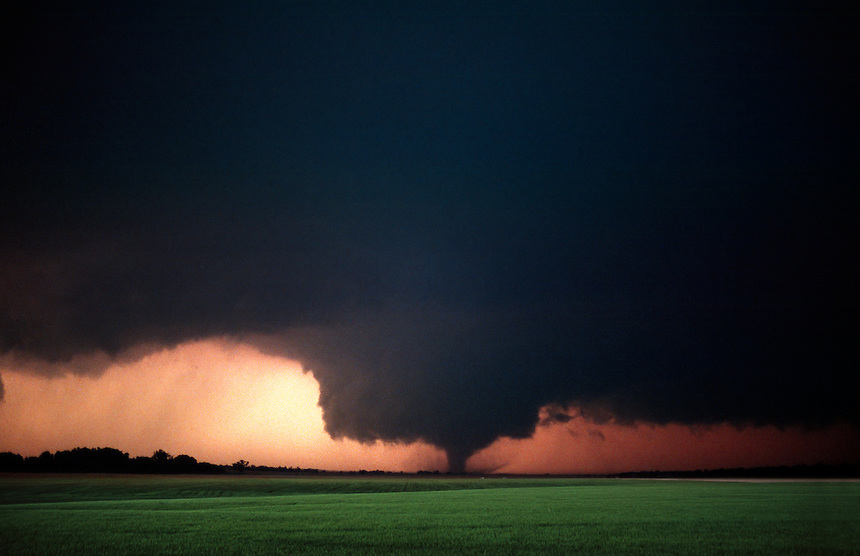 A strong tornado, pendant from a large wall cloud, rips across the countryside just after sunset near Conway Springs Kansas on May 29th, 2004.