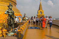 Bangkok, Thailand.  Donors to the Temple, led by a Monk, Circumambulate the Chedi, Guarded by the God of the Area of Wat Saket (Phu Khao Thong), the Golden Mount.