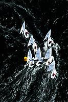 """Kieler Woche:EUROPA, DEUTSCHLAND, SCHLESWIG- HOLSTEIN 22.06.2005:Kieler Woche, Segler der Laser Klasse im Gedraenge an der Wende. <br /> Der Laser ist eine 4,23 m lange, 1,37 m breite und 57 kg (Rumpf) schwere Einmann-Jolle mit einem Segel.<br /> Der Laser wurde 1970 vom Amerikaner Bruce Kirby als Einhand-Jolle entworfen. Primaere Zielsetzung war damals ein Boot für die Freizeit zu entwerfen, deshalb auch der ursprüngliche Name """"Freetime"""".<br /> Seine einfache Bauweise und niedrige Anschaffungskosten führten zu einer raschen Ausbreitung. Ende des Jahres 2004 gab es ca. 180.000 Boote auf der Welt!<br /> Der Laser ist eine One-Design Bootsklasse und wird von der Firma Performance Sailcraft Ltd. in England gefertigt. Weiterhin gibt es Lizenznehmer in Australien und in Chile.<br /> Das Niveau in der Laser-Klasse gilt als eines der höchsten der olympischen Bootsklassen<br /> Luftaufnahme, Luftbild,  Luftansicht"""