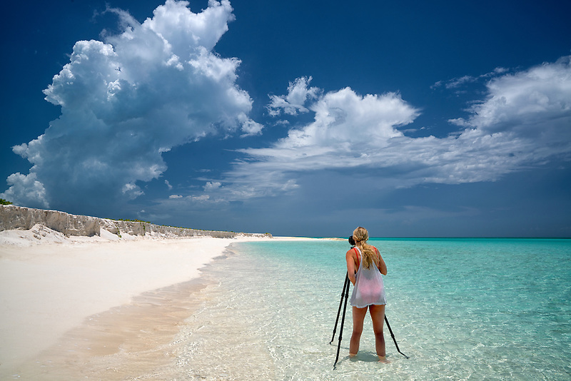 Photogrspher with white chaulk cliffs clouds and ocean. Admirals Point. Turks and Caicos