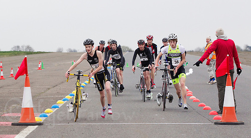 27 MAR 2011 - LOUGHBOROUGH, GBR - Competitors dismount at the end of the bike during the British Youth Mens Duathlon Championships (PHOTO (C) NIGEL FARROW)